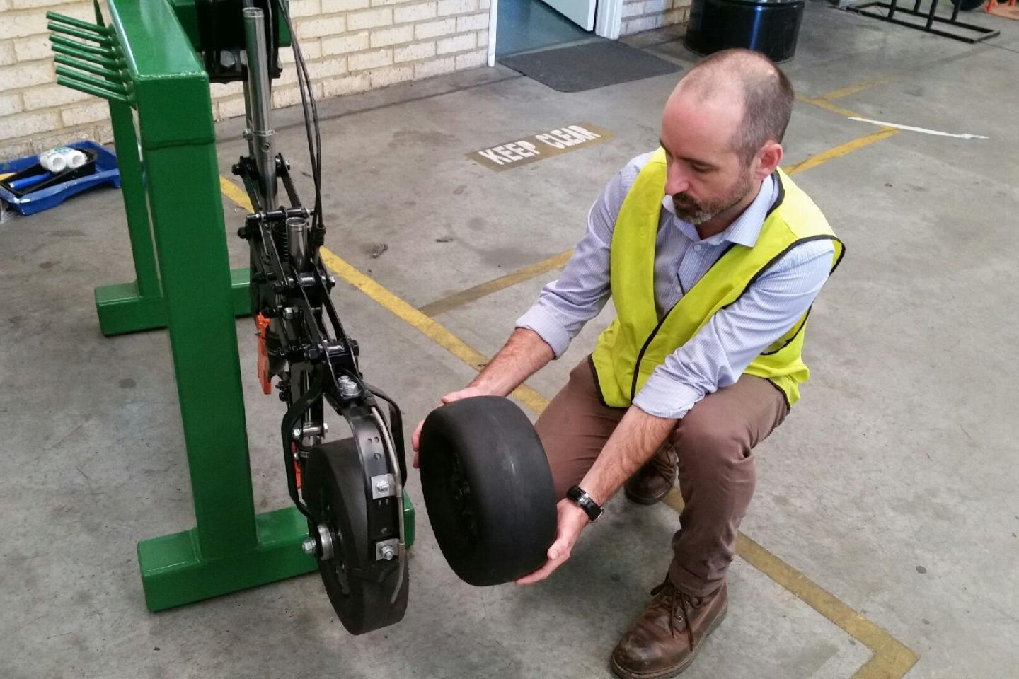 Ausplow engineering manager Carl Vance illustrates the difference between the new 135mm diameter press wheel and the standard diameter press wheel mounted on a DBS module.