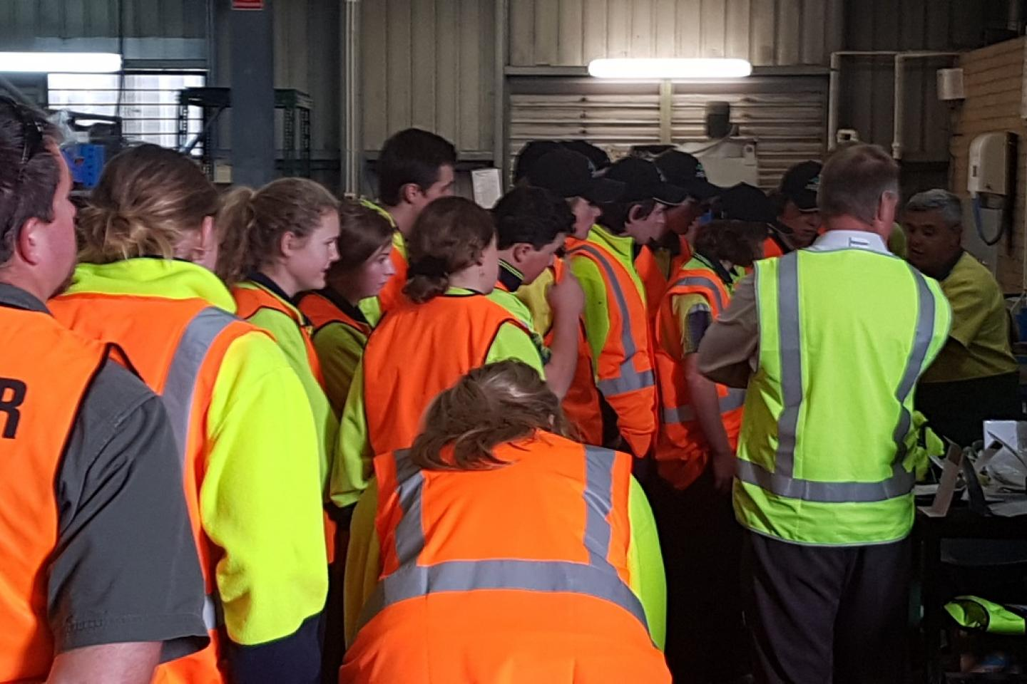 Students gather round to hear how stages of manufacture are accomplished.