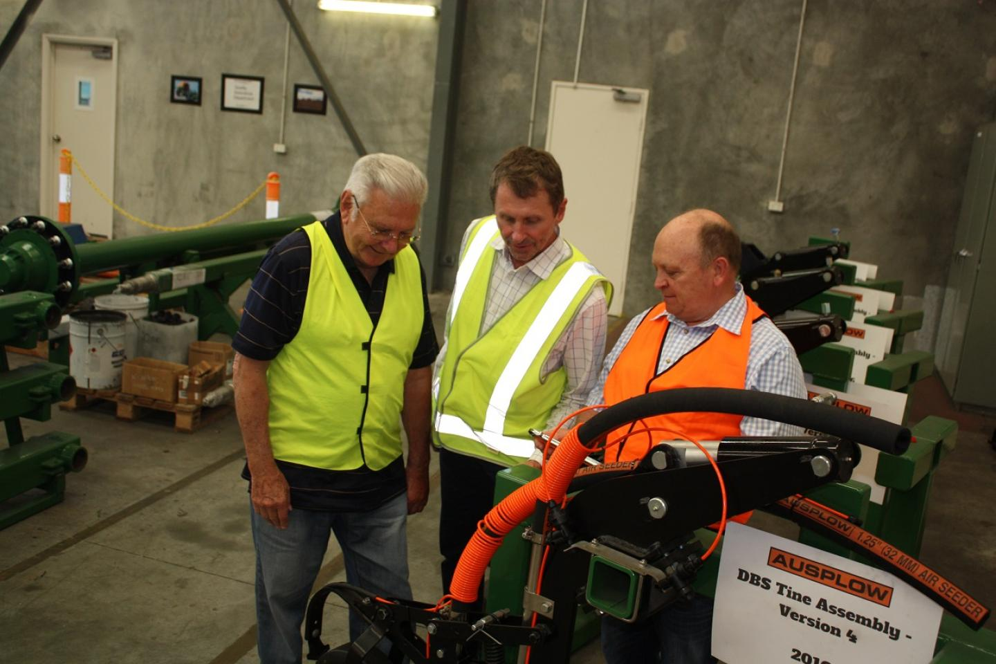 Ausplow managing director John Ryan (left), the company's sales and marketing manager Chris Blight and Nutrian director Dave Seagreen discuss the liquid delivery system on a DBS module during the factory tour with Primaries CRT agronomists at Jandakot this week.