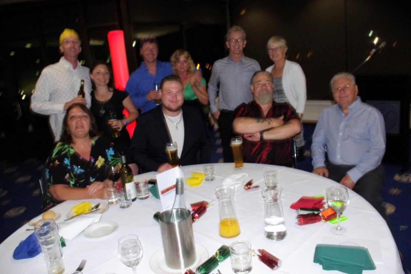 Maggi Di Re (left), Erich Nelson and Keisha Roberts (standing), Peter Hornsby, Mark and Theresa Bolton (standing), Mark Oliver and Carol Muir (standing), John Di Re and John Ryan AM.