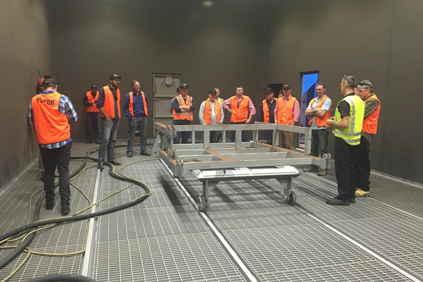 Ausplow factory manager Gary Andrews (yellow safety vest) explains the sand blasting process to a group of Swan Hill farmers during a recent factory tour.